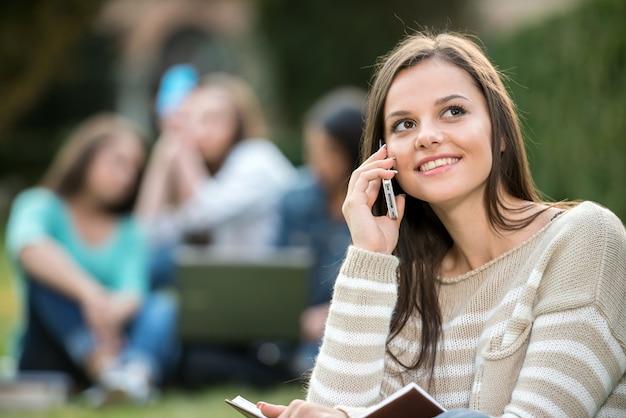 A menina está falando pelo telefone no parque verde.