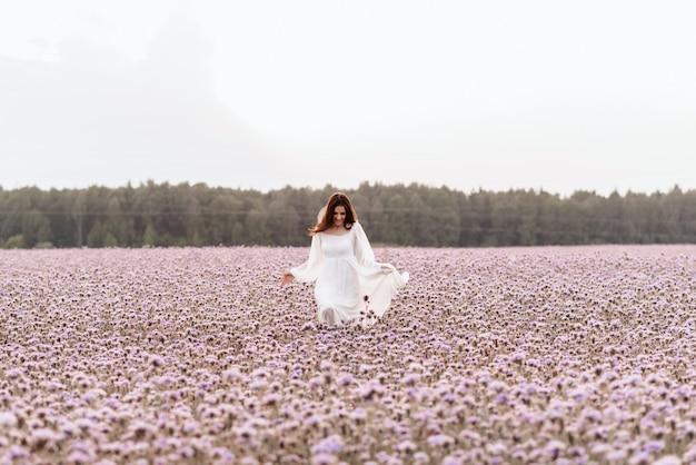 A menina está feliz e ri correndo pelo campo florido