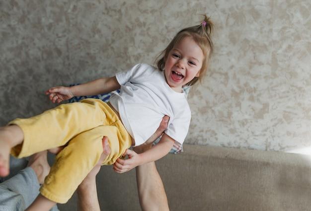A menina está feliz e rindo enquanto brinca com o pai em casa no sofá