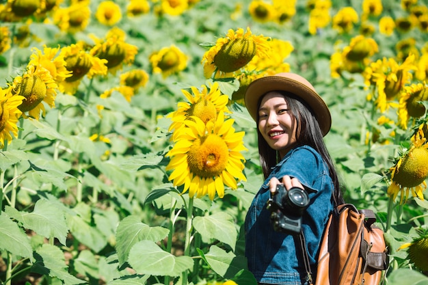 A menina está feliz em tirar fotos no campo de girassol.