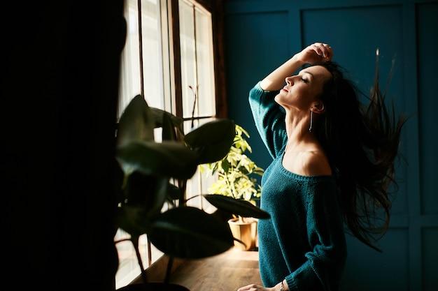 A menina está feliz por estar no sol da manhã em seu apartamento