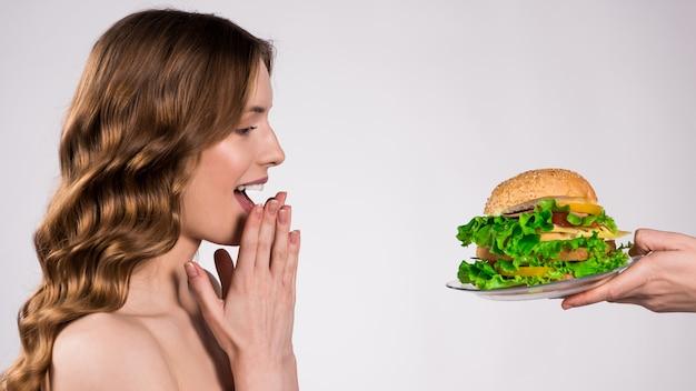 A menina está feliz sobre o hamburger isolado.
