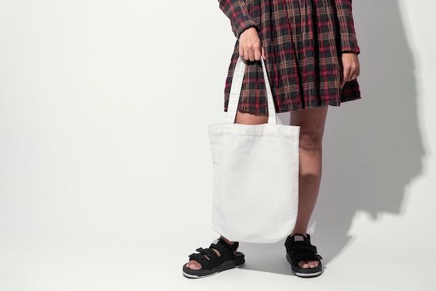 A menina está guardando o tecido da lona do saco.