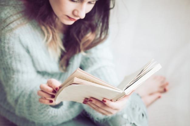 A menina está lendo um livro