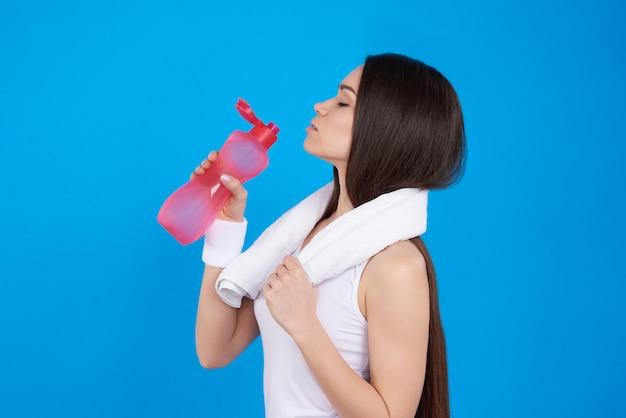 A menina está levantando com bebida da energia no fundo azul.