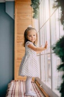A menina está perto da janela na véspera de natal