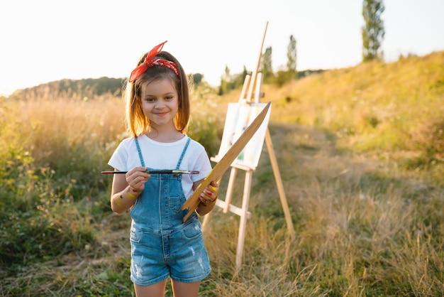A menina está pintando uma foto ao ar livre