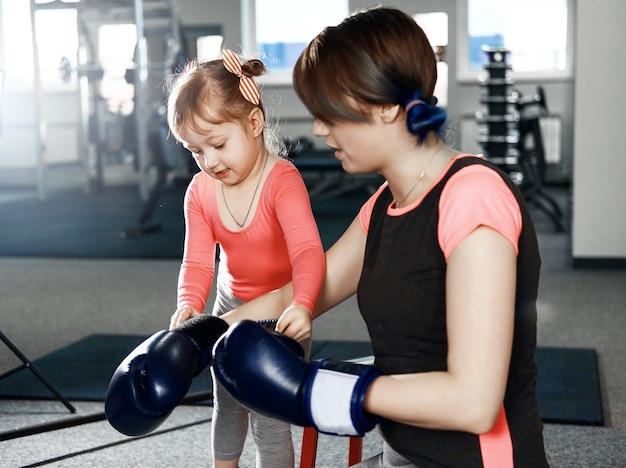 A menina está praticando boxe, a menina coloca luvas de boxe para a mãe, mãe e filha se preparando para a batalha