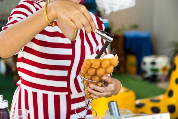 A menina está preparando uma sobremesa deliciosa sorvete waffle de hong kong