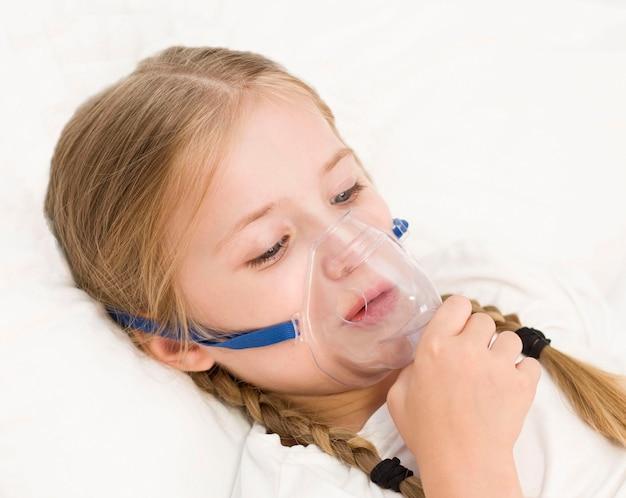 A menina está respirando por um inalador. uma criança doente está deitada na cama
