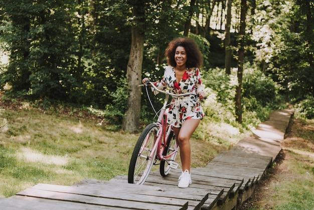 A menina está rolando a bicicleta na passagem de madeira.
