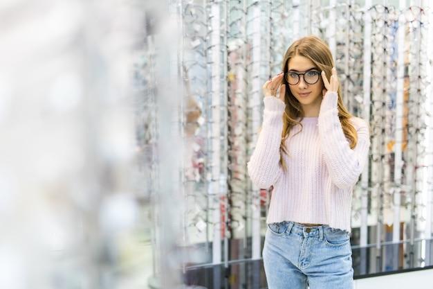 A menina está se preparando para os estudos na faculdade e experimenta novos óculos para seu visual perfeito em uma loja profissional