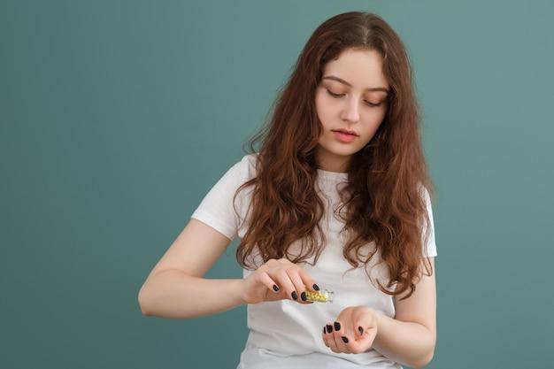 A menina está se preparando para tomar valeriana em comprimidos, coloca alguns dos comprimidos em sua mão