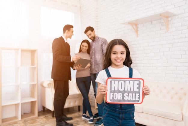 A menina está segurando o sinal com a inscrição: home for sale
