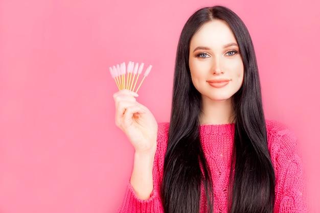 A menina está segurando os cílios, um modelo com maquiagem, sobre um fundo rosa. mestre de maquiagem conceito, rímel ou extensão dos cílios.