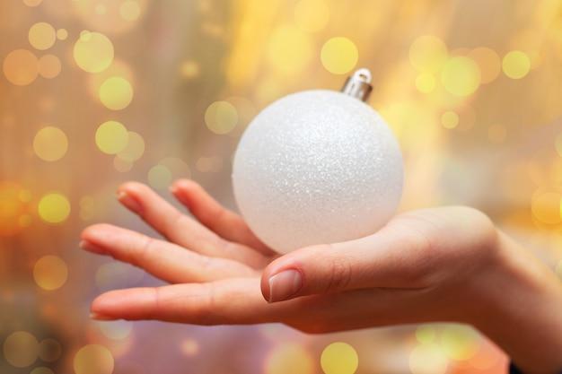 A menina está segurando um brinquedo de árvore de natal, feriado de ano novo e natal