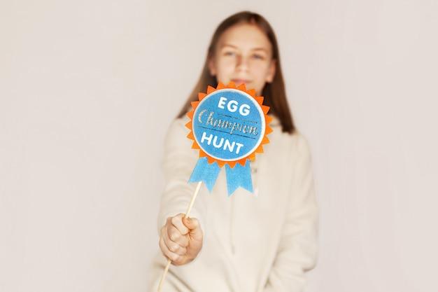A menina está segurando um cartaz caçando ovos fita