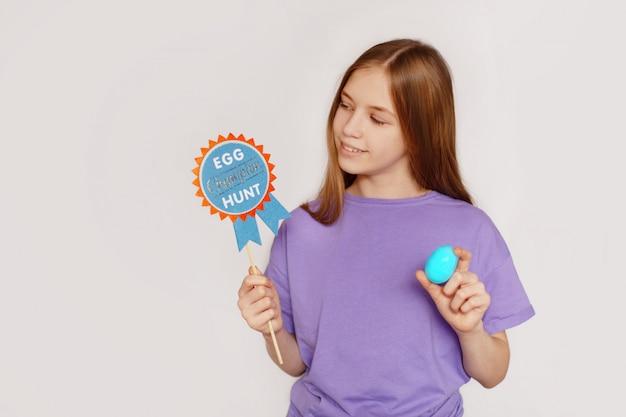 A menina está segurando um cartaz de caça à fita de ovos e ovo de páscoa