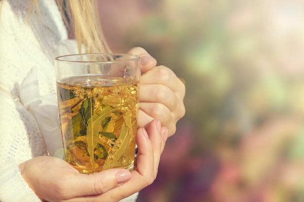 A menina está segurando um close-up de chá quente de aquecimento.