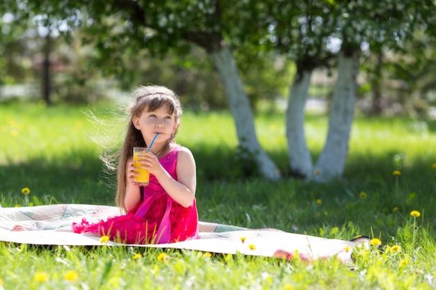 A menina está segurando um copo com suco nas mãos dela.