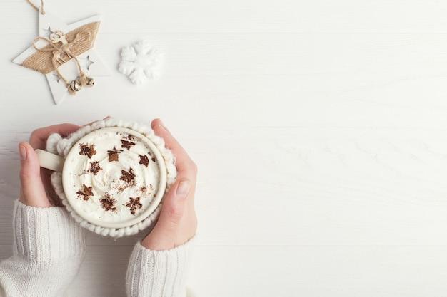 A menina está segurando um copo de bebida quente de inverno, com chantilly e pó em forma de estrelas
