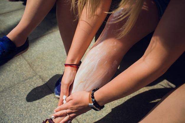 A menina está segurando um pote de creme hidratante nas mãos. ela esfrega os pés com os dedos.