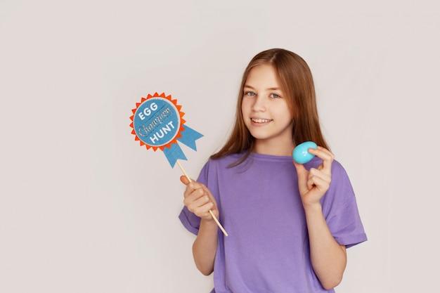 A menina está segurando uma placa de caça aos ovos e ovo de páscoa