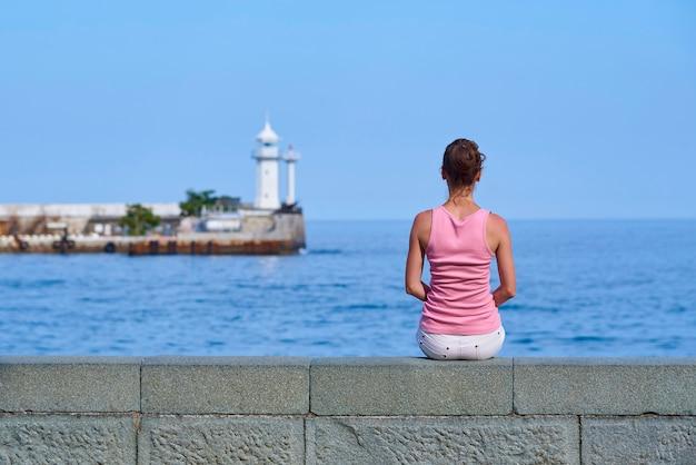 A menina está sentada à beira-mar e está olhando para a distância até o farol.