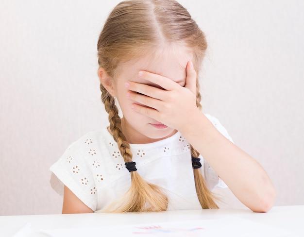 A menina está sentada à mesa com a mão no rosto
