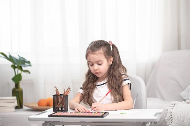 A menina está sentada à mesa e fazendo lição de casa.