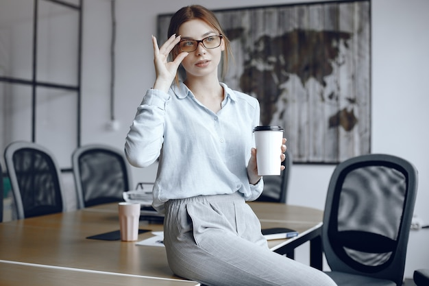 A menina está sentada à mesa. mulher segurando uma xícara. luneta ajusta os óculos