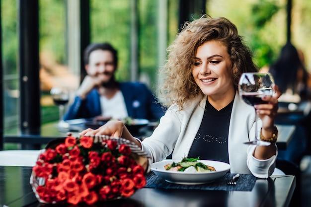 A menina está sentada à mesa no restaurante e bebe vinho, desfruta de um buquê de flores de rosas vermelhas e espera um encontro