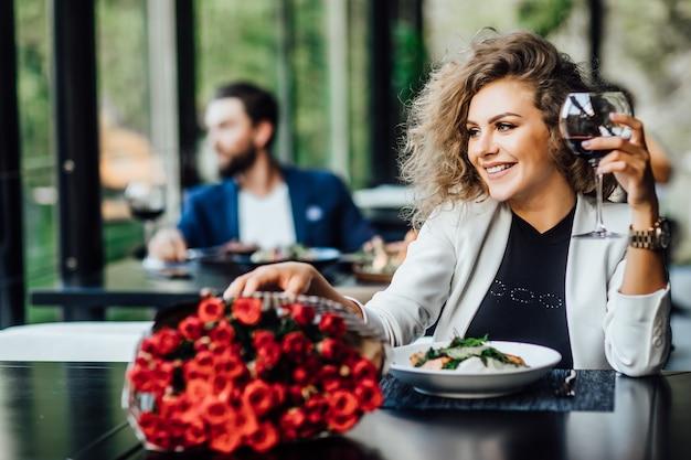 A menina está sentada a uma mesa no restaurante e bebe vinho, aprecia o perfume da flor de rosas e espera um encontro
