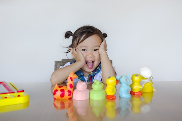 A menina está sentada e feliz com os brinquedos na frente.