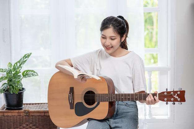 A menina está sentada e tocando violão na cadeira.
