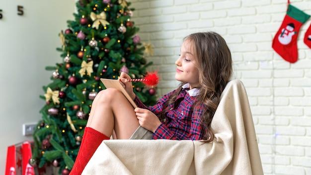 A menina está sentada em uma cadeira e escrevendo uma carta em casa, árvore de natal na parede