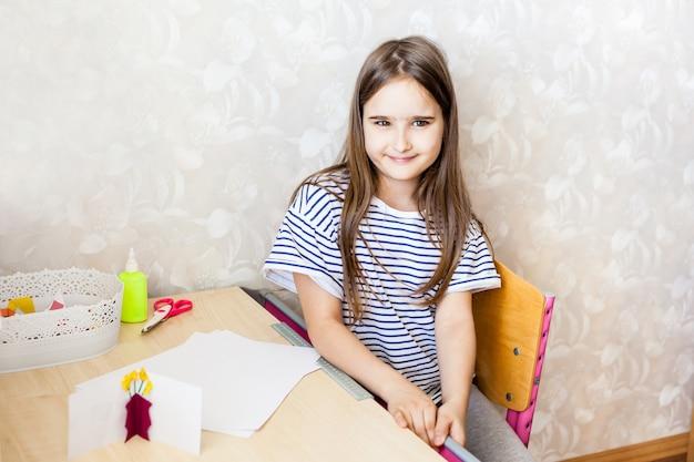A menina está sentada em uma mesa, desenhando, fazendo lição de casa, arrumando, escrevendo, papel, marcadores