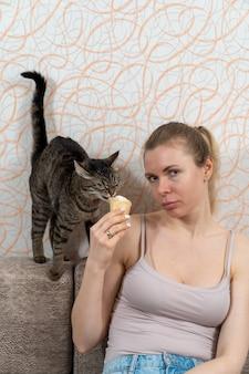 A menina está sentada no sofá segurando um sorvete em um copo de waffle na mão e a gatinha resolve provar esta iguaria