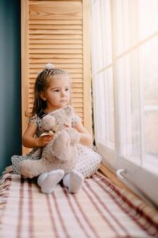 A menina está sentada perto da janela com o urso de brinquedo