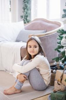 A menina está sentada perto do sofá e decorada com árvore de natal, a sala está decorada para o natal