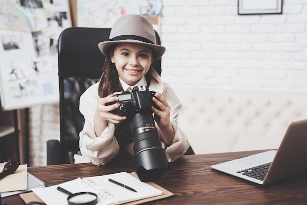 A menina está sentado na mesa olhando fotos na câmera.