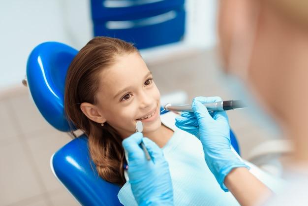 A menina está sentando-se em uma cadeira dental na recepção de um dentista.