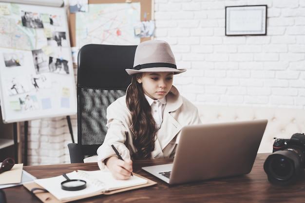 A menina está sentando-se na mesa que toma notas perto do portátil.
