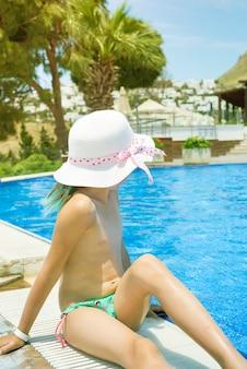 A menina está sentando-se na piscina lateral com água azul, férias de verão.