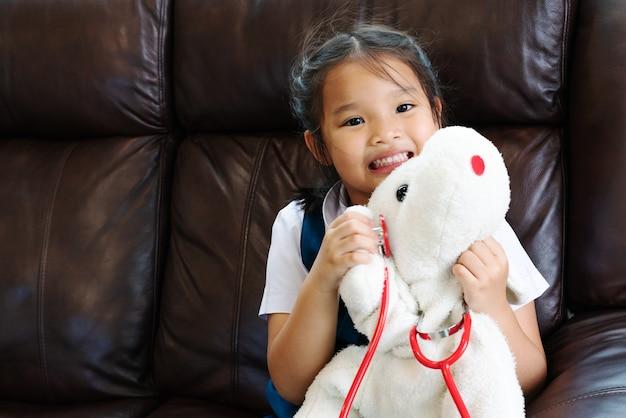 A menina está sorrindo e jogando o doutor com estetoscópio. kid e conceito de cuidados de saúde.