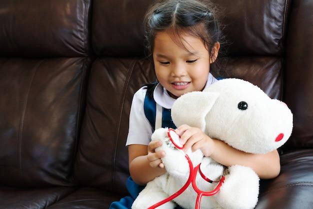 A menina está sorrindo e jogando o doutor com estetoscópio.