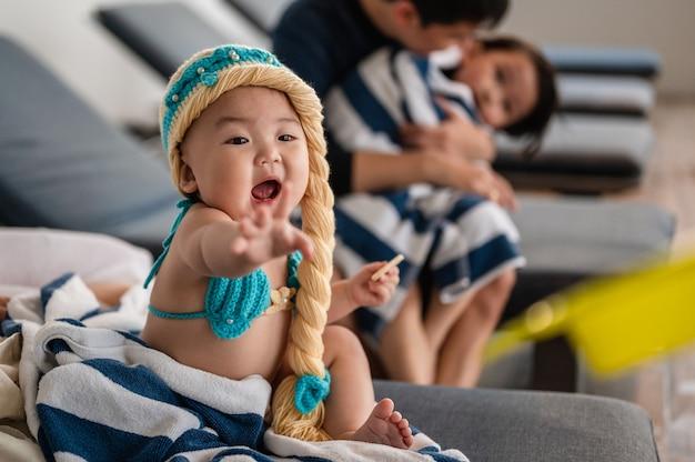 A menina está tentando pegar o brinquedo que os pais dela deram na frente do pai e do filho.