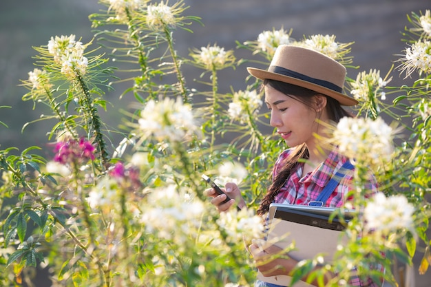 A menina está tirando fotos de flores com uma câmera móvel.