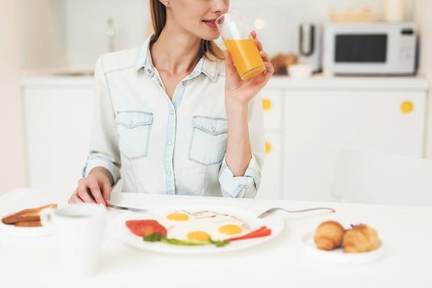 A menina está tomando café da manhã na cozinha.