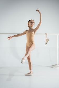 A menina está treinando perto da barra de balé.